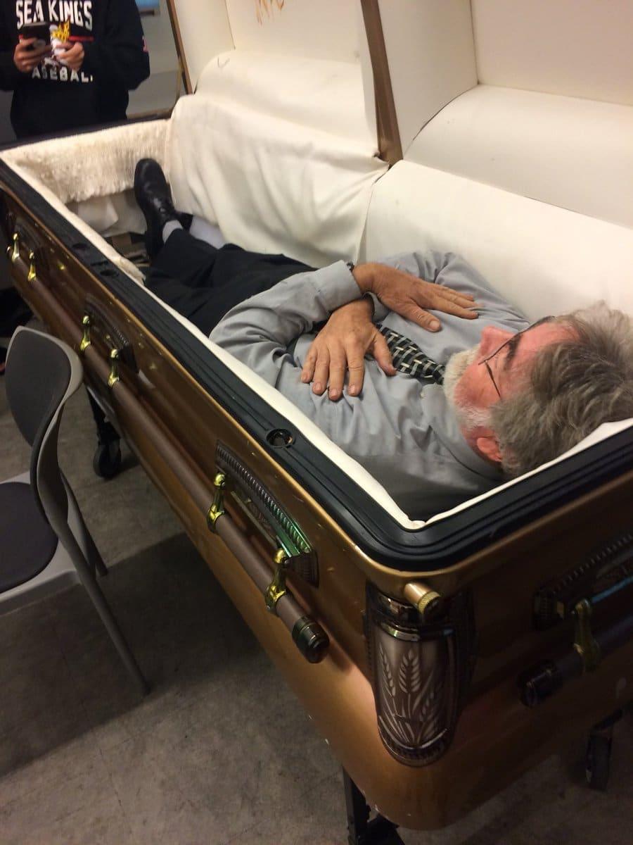 мужчина лежит в гробу