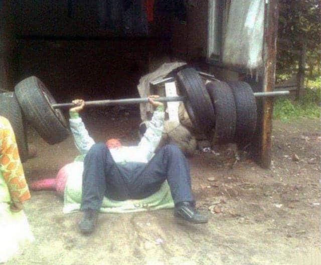 мужчина жмет штангу с колесами