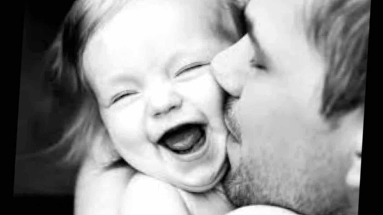 отец целует дочь в щеку