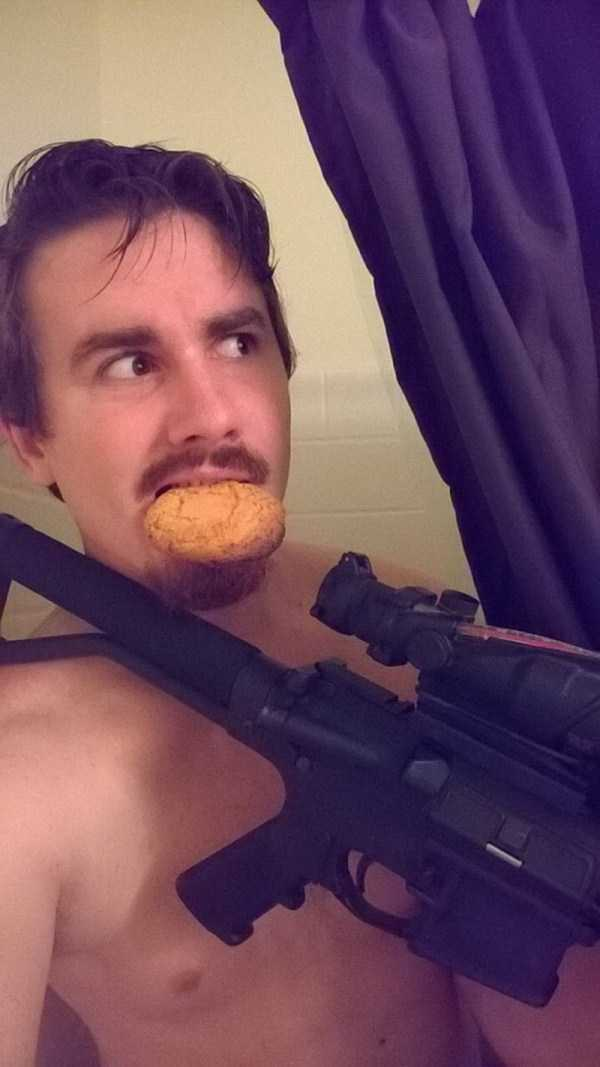 мужчина с винтовкой и печеньем во рту