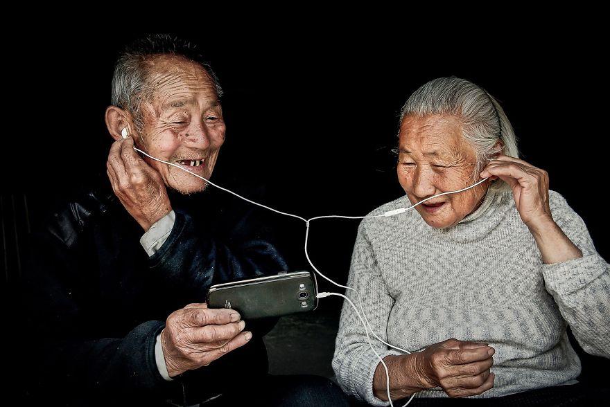 бабушка и дедушка с наушниками слушают смартфон