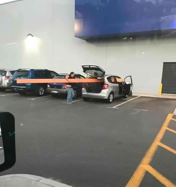 парень укладывает доску в авто