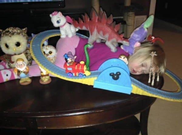 девочка спит в игрушках на столе