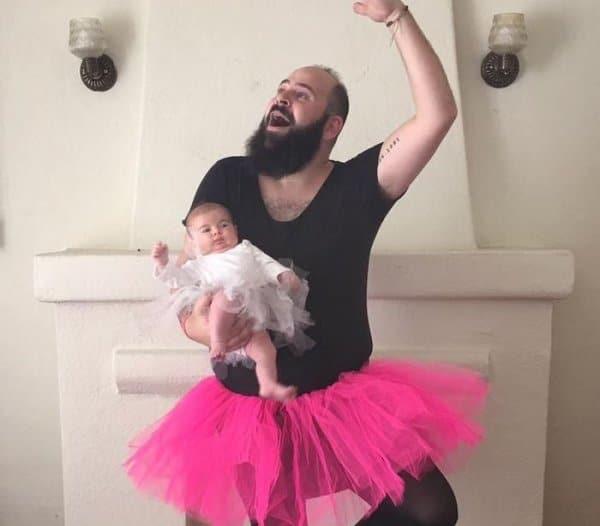бородатый мужчина в балетной пачке с ребенком на руках