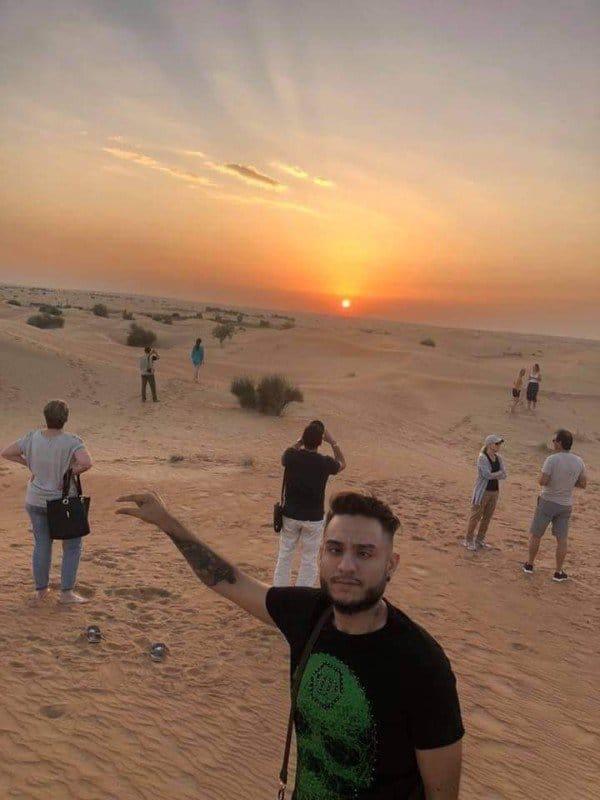 парень фотографируется на фоне заката