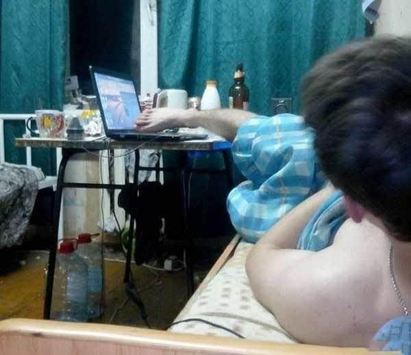 парень нажимает кнопки на ноутбуке ногой