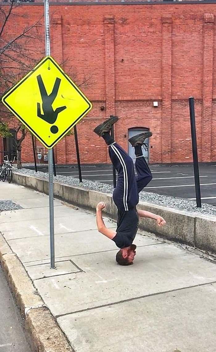 мужчина стоит на голове рядом со знаком