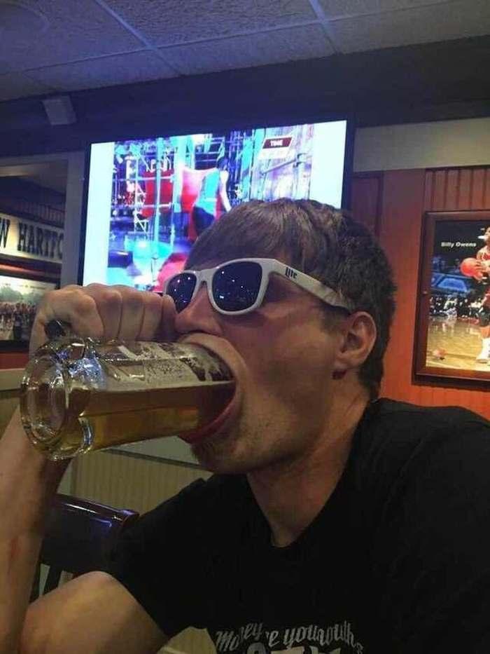 парень в очках пьет пиво из бокала