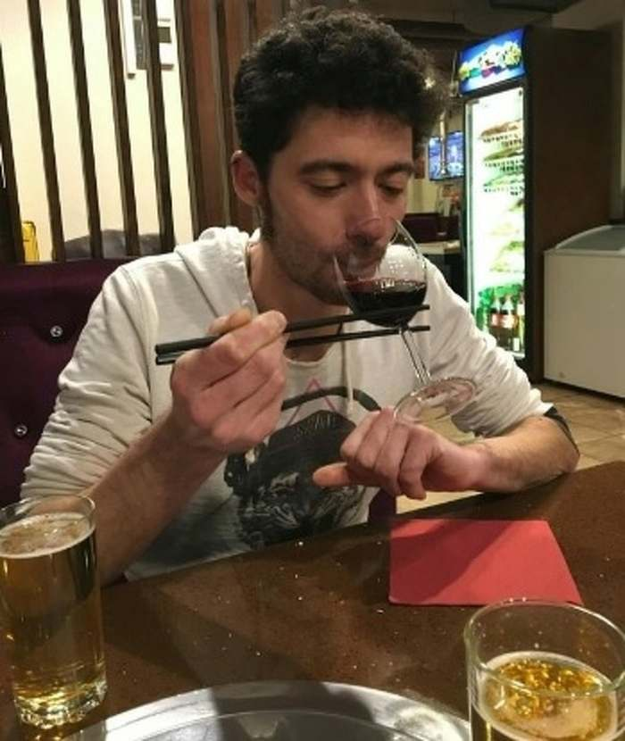 парень пьет вино с помощью палочек