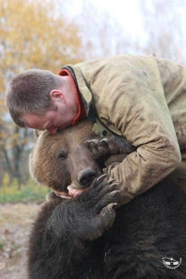 мужчина обнимает медведя