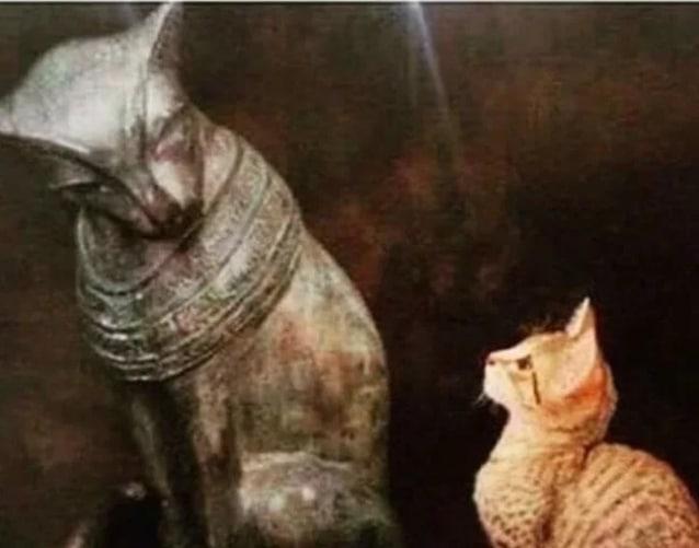 рыжий котенок рядом со статуэткой кошки