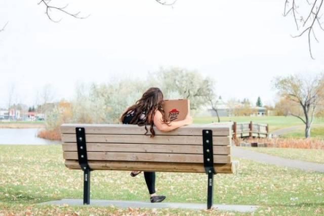 девушка с пиццей сидит на скамейке