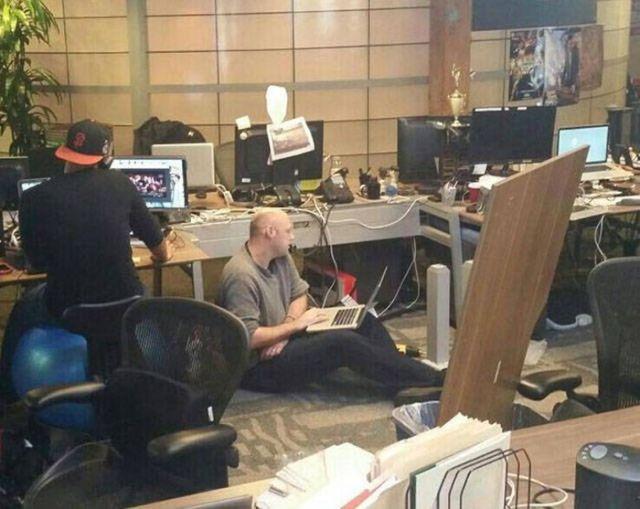 мужчина с ноутбуком на полу в офисе