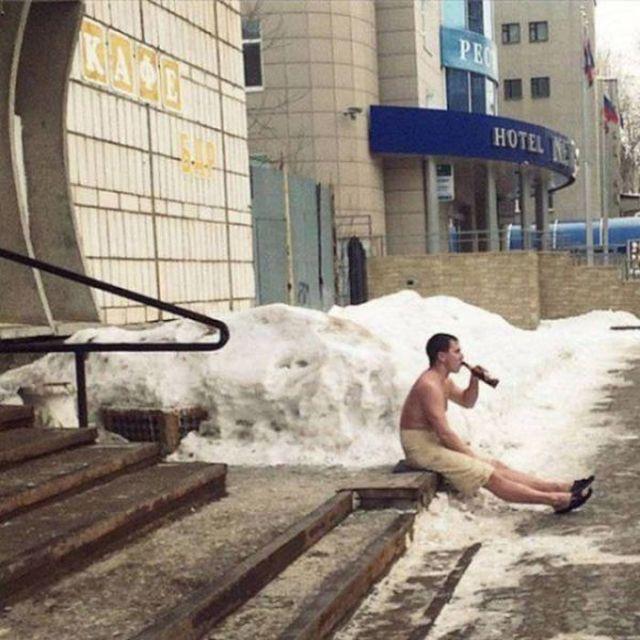 парень пьет пиво, сидя в полотенце на крыльце
