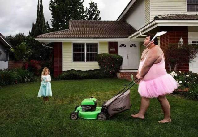 мужчина в розовом стрижет газон