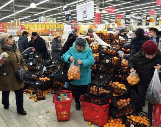 люди набирают мандарины в супермаркете