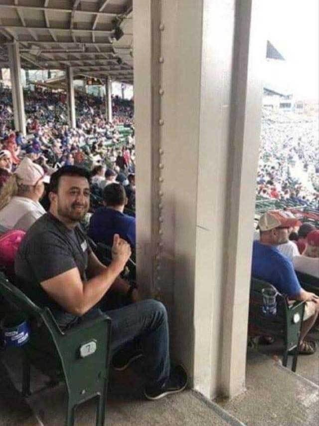 мужчина сидит за колонной на стадионе