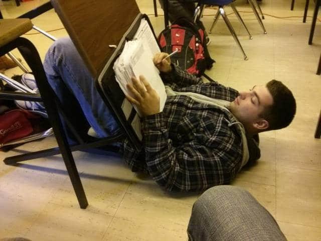 парень пишет лежа на полу