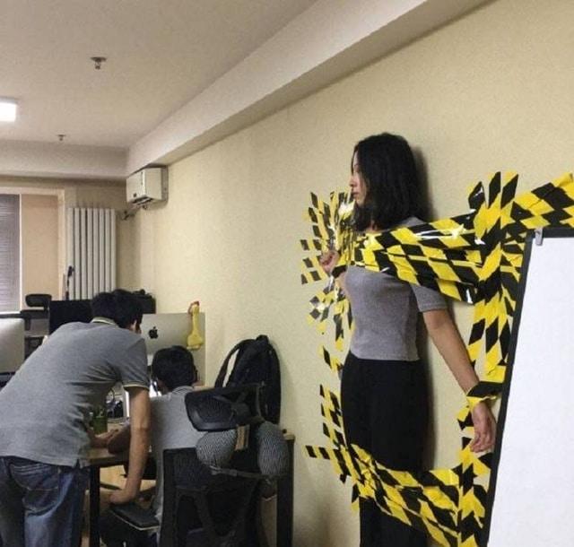 девушка приклеена к стене лентой