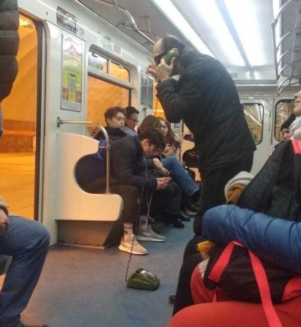 мужчина говорит по городскому телефону в метро