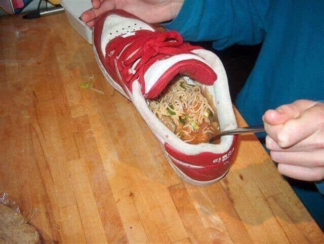 парень ест лапшу из кроссовка