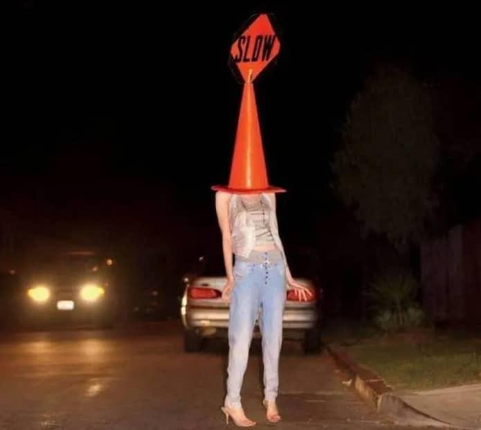 девушка с дорожным конусом на голове