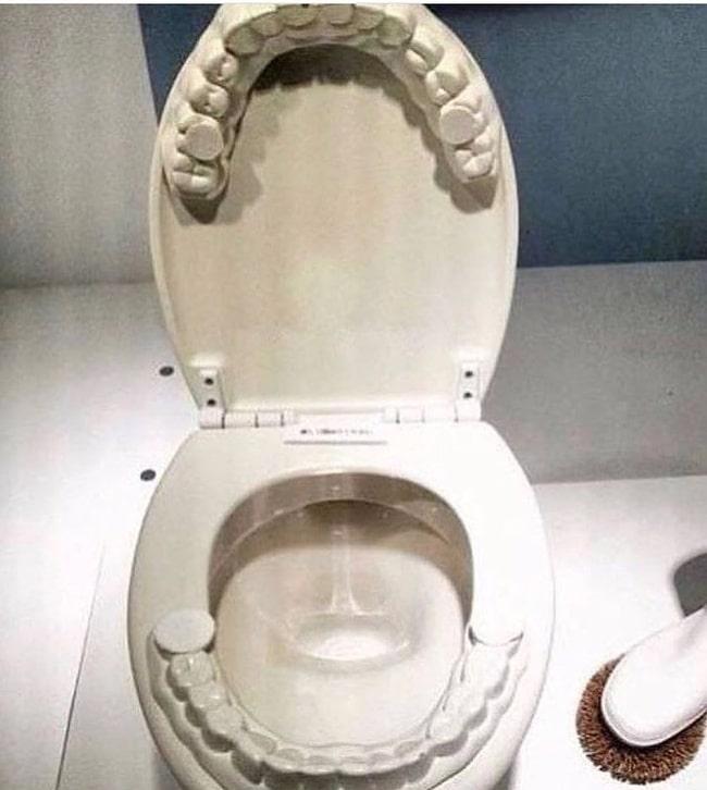 Унитаз, на ободке которого зубы