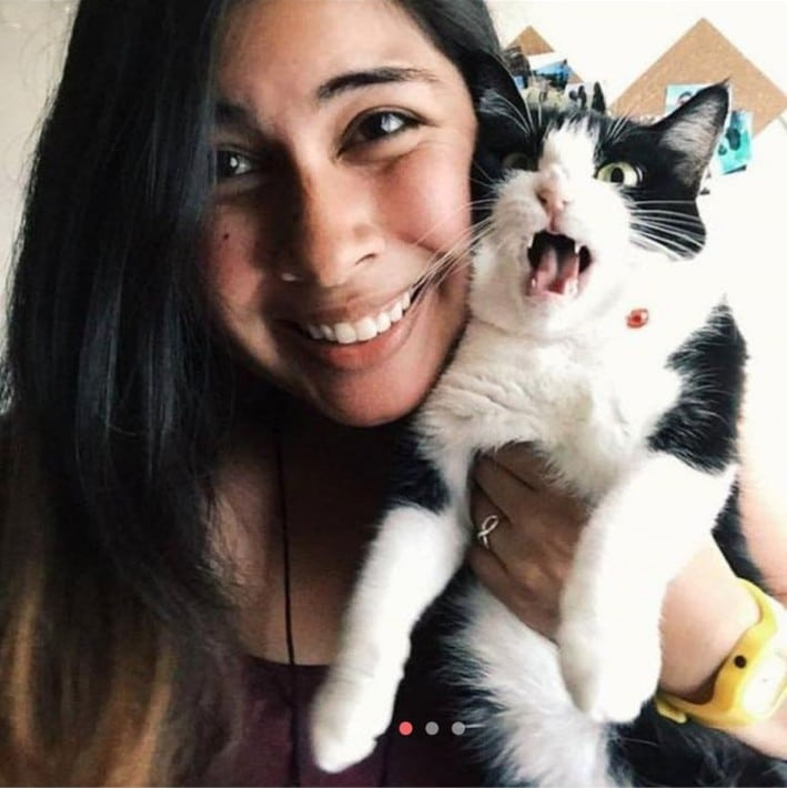девушка обнимает черно-белого кота