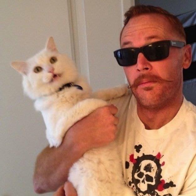 мужчина держит на руках белого кота