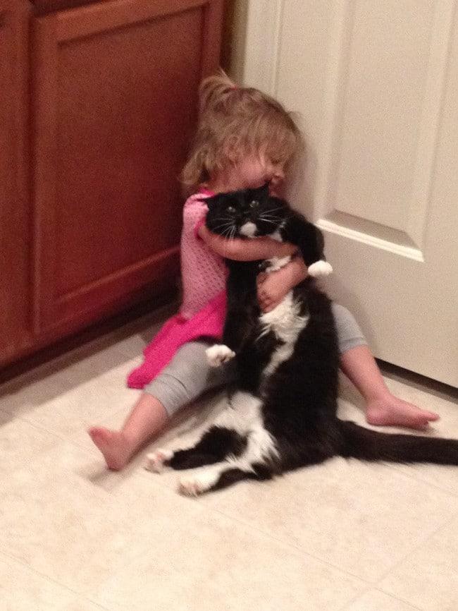 девочка сидит в обнимку с черным котом