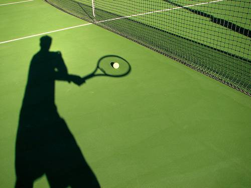 тень теннисиста на корте