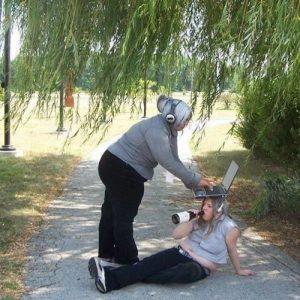 девушка сидит на земле с ноутбуком на голове