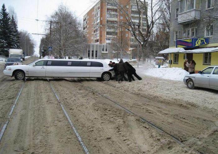 мужчины толкают лимузин через рельсы