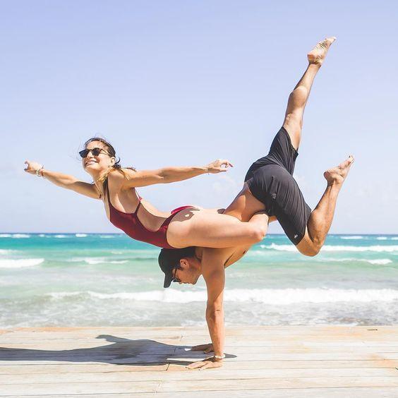 парень и девушка занимаются йогой у моря