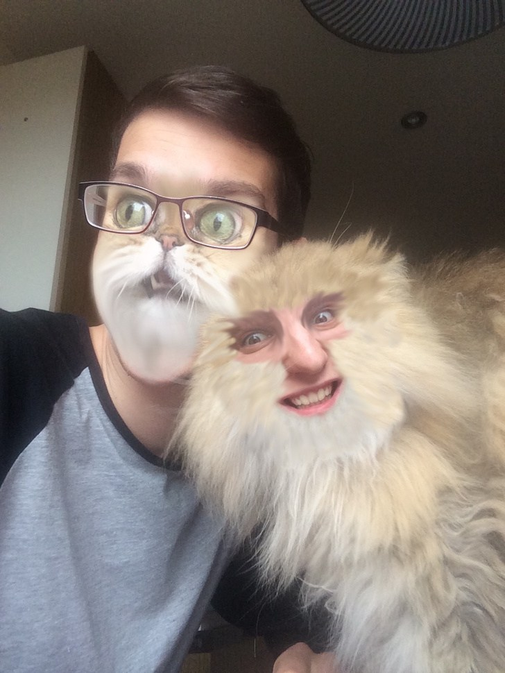 парень в очках с пушистым котом