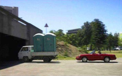 грузовик с биотуалетами и красный кабриолет