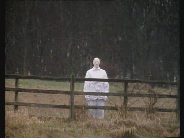 мужчина в белом за забором