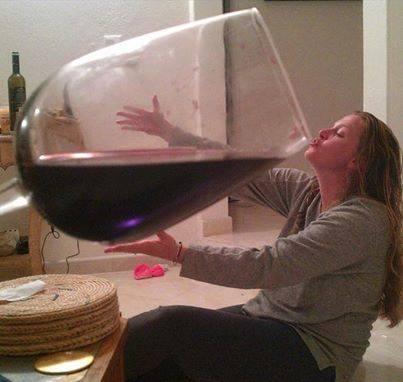 девушка пьет из огромного бокала