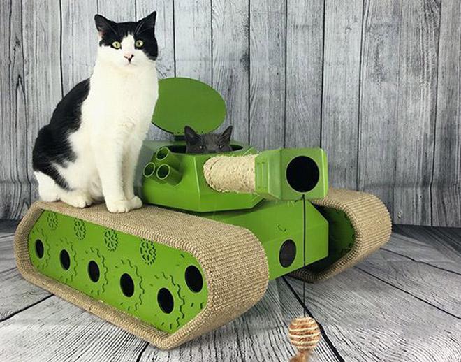 черно-белый кот сидит на игрушечном танке