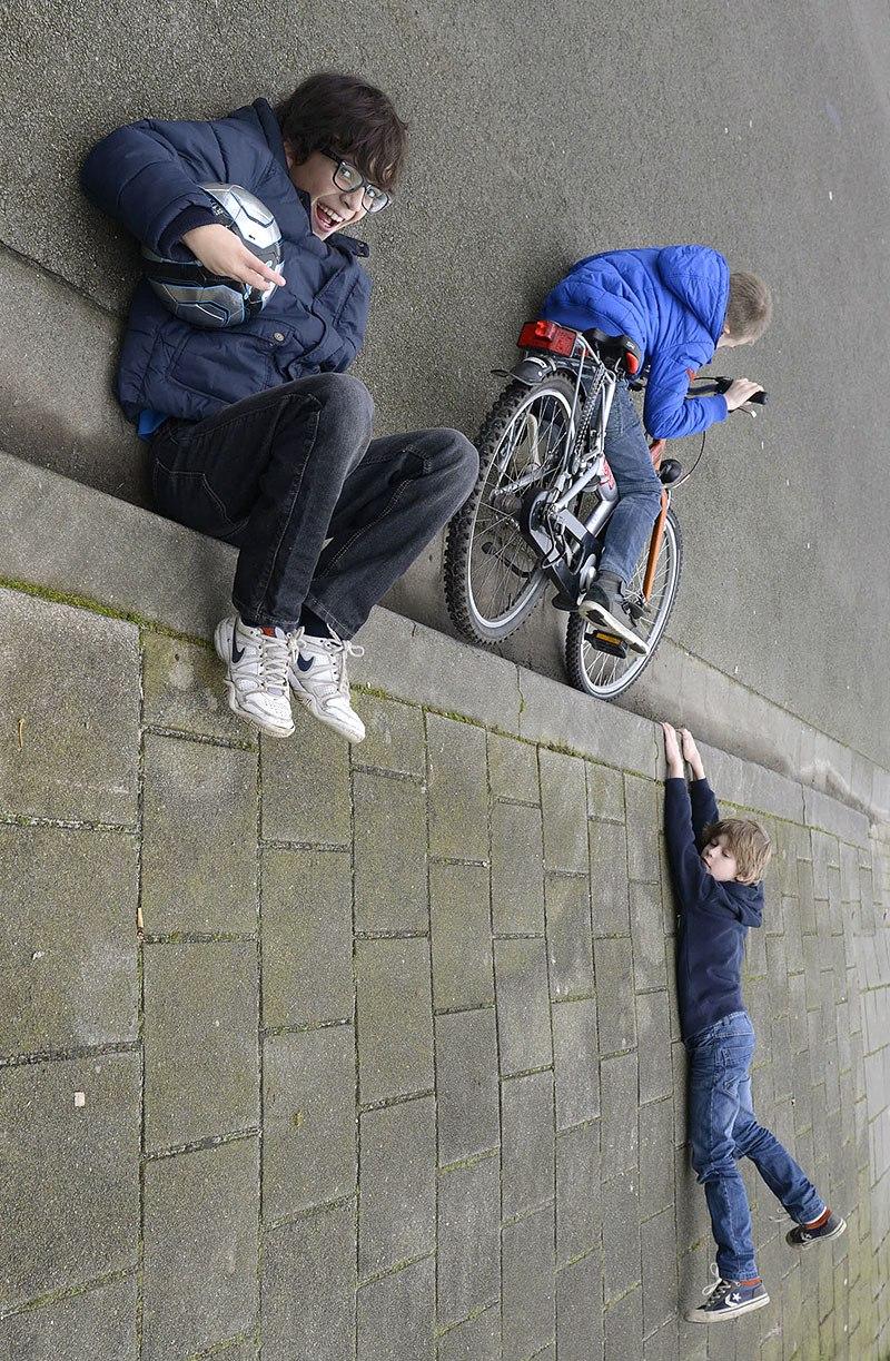 мальчики лежат на тротуаре