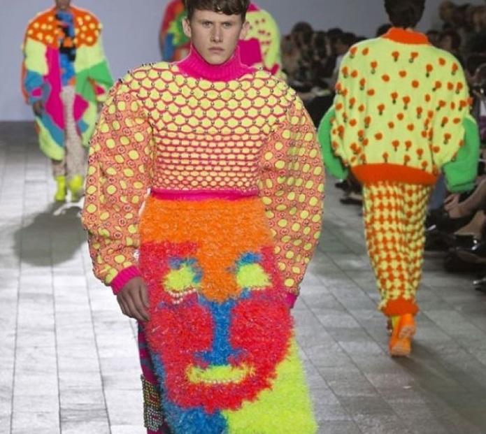 парень в ярком объемном свитере на подиуме