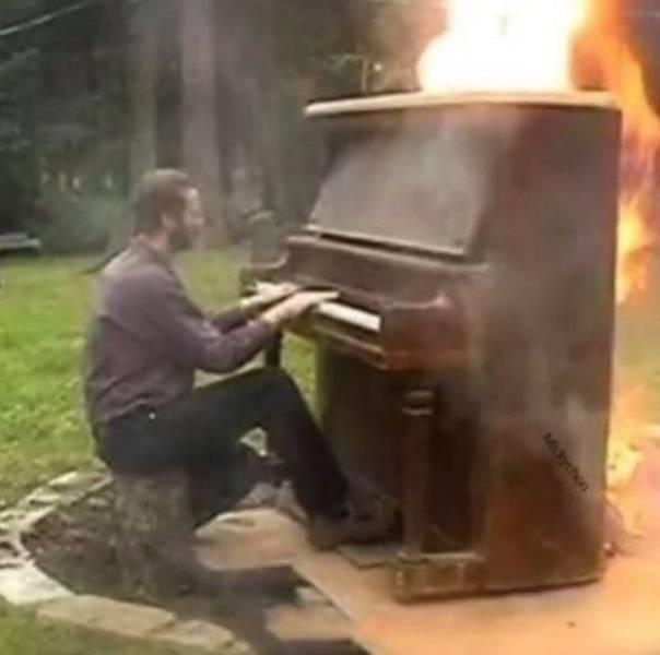 Человек играет на горящем пианино
