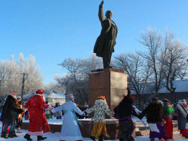 Люди водят хоровод вокруг памятника Ленину