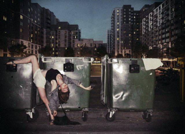 Девушка танцует возле мусорных баков