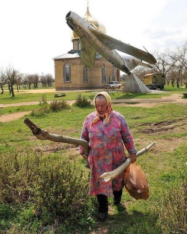 Бабуля с большими бревнами идет по своим делам