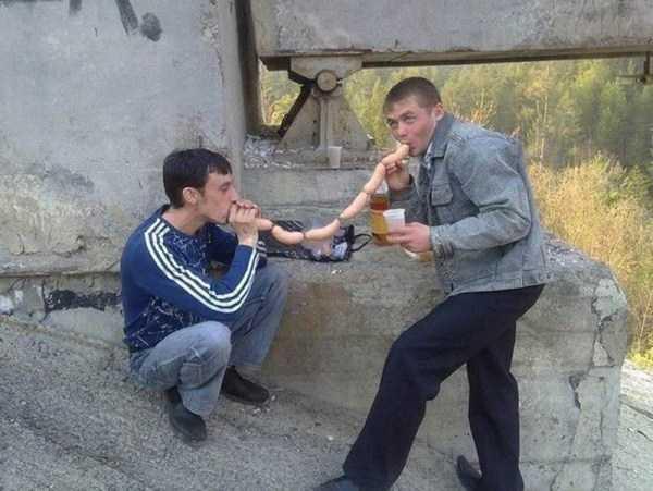 парни едят сардельки на улице