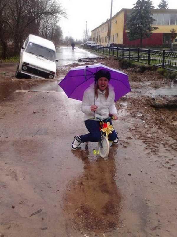 девушка под зонтом на трехколесном велосипеде