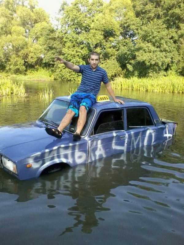 парень сидит на утонувшей машине
