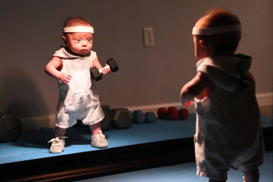 маленький мальчик с гантелей в руке