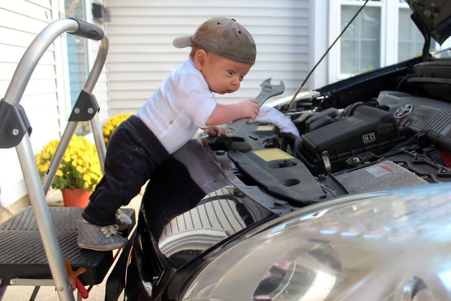 маленький мальчик под капотом машины